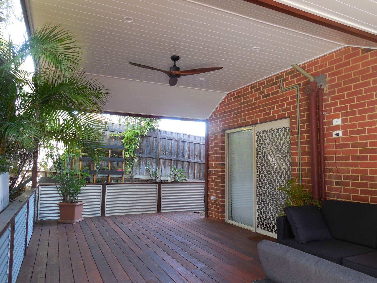 Decked & Fenced Patio With Ceiling Fan, Attached To A Brick Home.